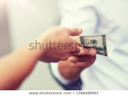 Businessman giving bribe money dollar banknotes in hands to part Stock photo © snowing