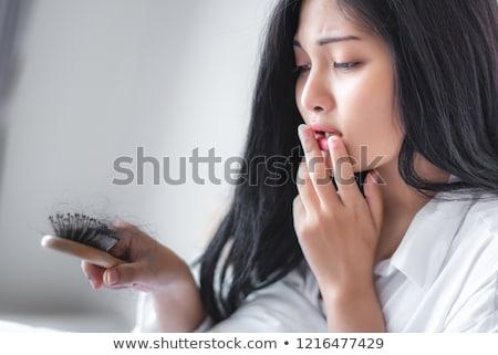 pretty woman combing her long black hair Stock photo © imarin