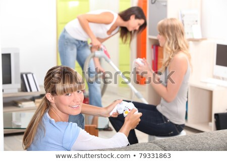 a woman vacuuming and two women playing video games Stock photo © photography33