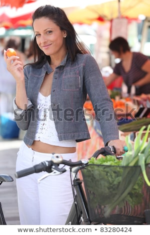 Woman eating a clementine while standing with her bike at a market Stock photo © photography33