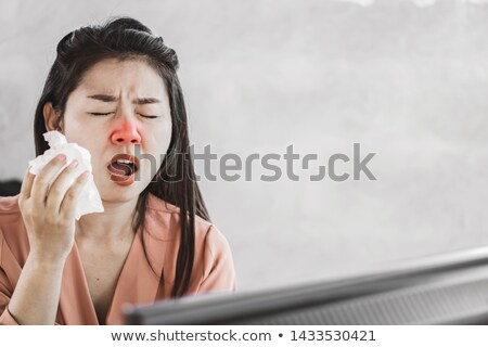 Professional sitting at desk sneezing into tissue Stock photo © stockyimages