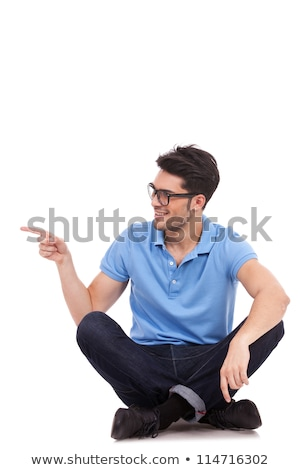 young man sitting and pointing sideways Stock photo © feedough