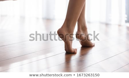 Pretty woman standing on tiptoe at home  Stock photo © deandrobot