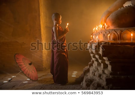 Buddhist novices praying with candlelight in temple Stock photo © szefei