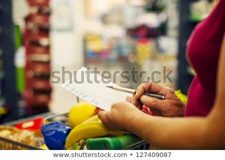 Woman read shopping list and pushing cart Stock photo © bluering