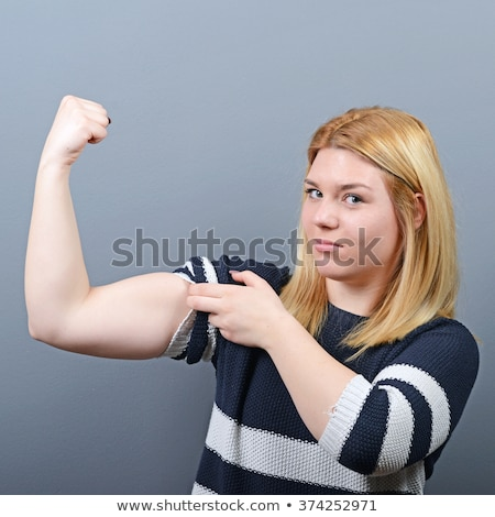 Cheerful pretty fitness woman showing her biceps. Stock photo © deandrobot