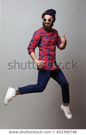 vertical image of cool hipster posing in studio stock photo © deandrobot