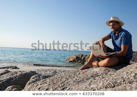 Man sitting on the rocks and using laptop at the sea coast Stock photo © wavebreak_media