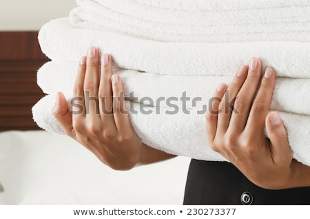 Maid holding towels in hotel room smiling Stock photo © monkey_business
