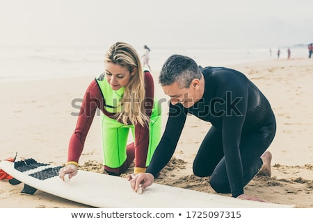 Man waxing surfboard with couple smiling Stock photo © IS2