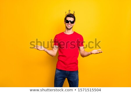 handsome young man wearing a denim shirt holds his sunglasses Stock photo © feedough