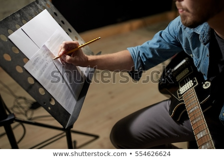 musician with guitar and music book at studio Stock photo © dolgachov