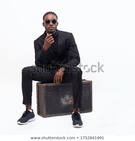 portrait of relaxed seated man wearing a black suit stock photo © feedough