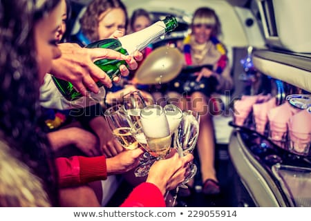 Celebration in a limo, woman and men drinking champagne Stock photo © Kzenon