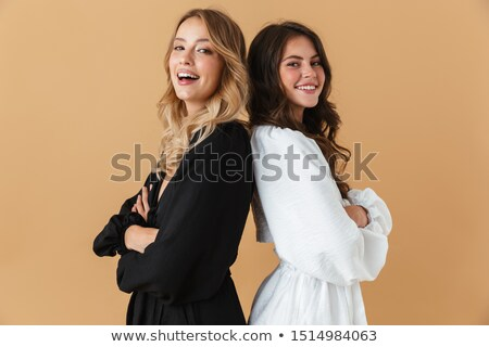 Two pretty delighted young girls friends standing Stock photo © deandrobot