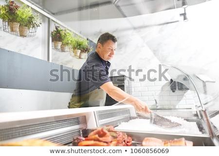 male seller adding ice to fridge at fish shop Stock photo © dolgachov