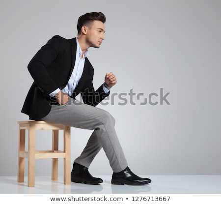 curious businessman sitting on wooden chair looks to side stock photo © feedough