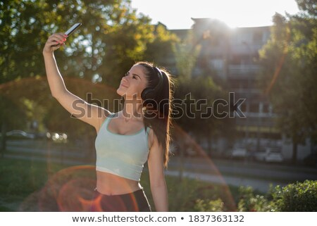 Photo of young caucasian sportswoman 20s in tracksuit stretching Stock photo © deandrobot