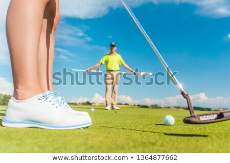 Zdjęcia stock: Golf ball on the putting green behind the low section of a female player