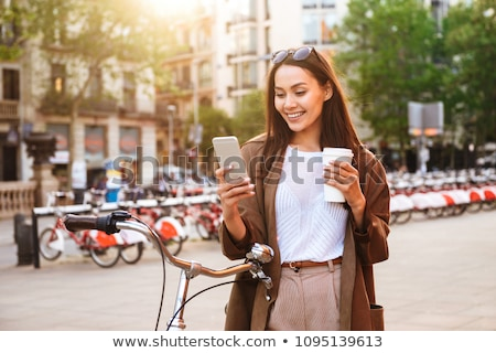 Stock photo: Woman outdoors with bicycle on the street chatting by mobile phone drinking coffee.