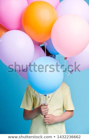 Little child in yellow shirt hiding behind bunch of birthday balloons Stock photo © pressmaster