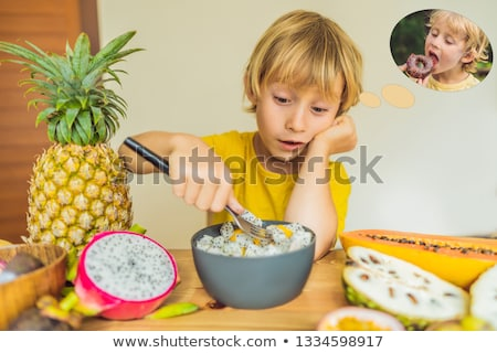 Boy eats fruit but dreams about donuts. Harmful and healthy food for children. Child eating healthy  Stock photo © galitskaya
