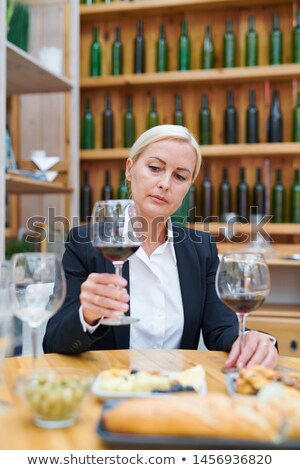 Serious blonde female professional sommelier looking at red wine in wineglass Stock photo © pressmaster