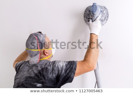 Plasterer smoothing interior wall with machine Stock photo © Kzenon