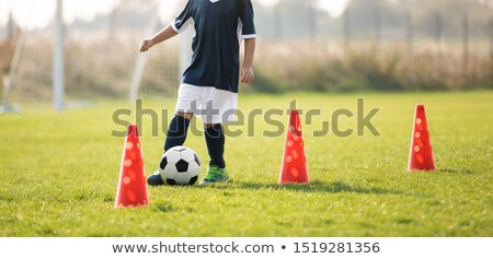 Soccer player dribbling through cones in the ground on a sunny.  Stock photo © matimix