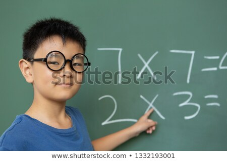 Front view of a smart Asian schoolboy doing math on greenboard in a classroom at elementary school Stock photo © wavebreak_media