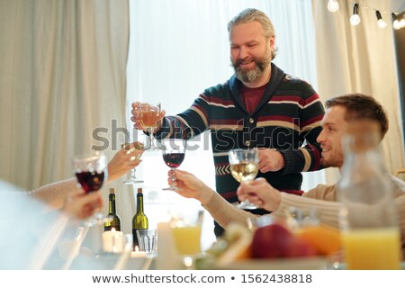 Smiling mature man clinking with glass of wine with other family members Stock photo © pressmaster