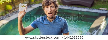 Man shows Dirt from the pool on a napkin BANNER, LONG FORMAT Stock photo © galitskaya
