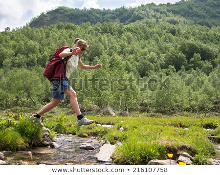 Woman hiking jumping over a creek in spring Stock photo © Kzenon