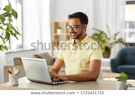 Stock photo: man working on a laptop at home.
