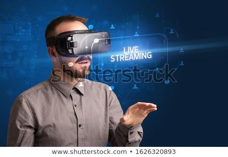 Businessman looking through Virtual Reality glasses, social media concept Stock photo © ra2studio