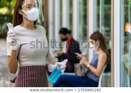 Waitress with face mask and face shield hold thermometer  Stock photo © vichie81