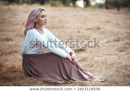 Portrait of smiling young girl sitting on grass in the forest an Stock photo © HASLOO