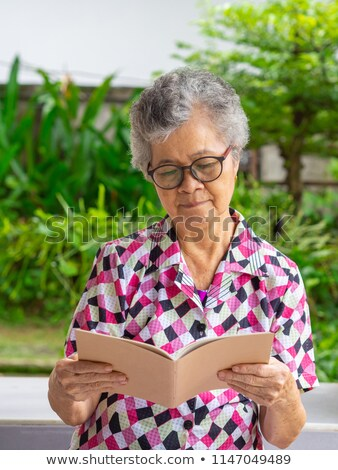 asian old woman read a book outdoor stock photo © ampyang