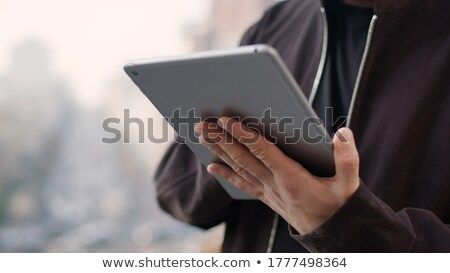 Man on street looking up, hold tablet computer in hands stock photo © adamr
