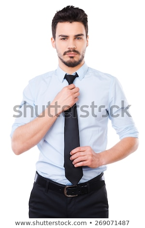 young businessman standing adjusting his tie stock photo © stryjek