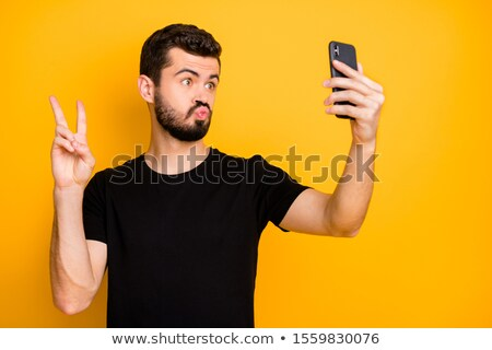 casual young man shows victory over the phone stock photo © feedough