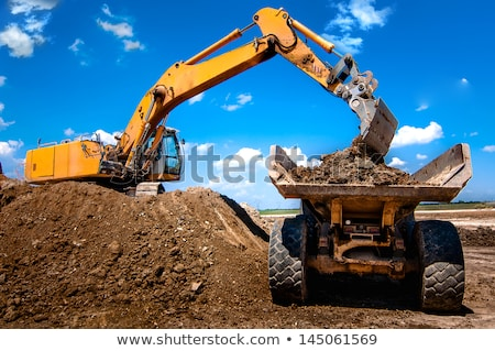 excavator loading dumper truck tipper in sandpit in highway construction site stock photo © papa1266