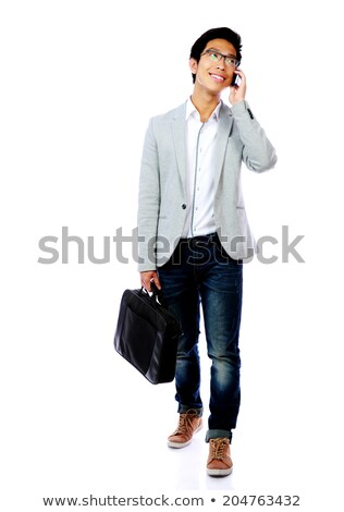 Full length portrait of asian man walking with laptop bag and speaking phone Stock photo © deandrobot