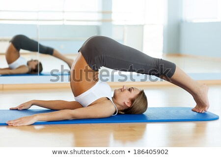 Young woman in sport cloths lying on the yoga mat and smiling Stock photo © deandrobot