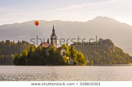 catholic church in bled lake and bled castle slovenia with hot air balloon flying at sunrise stock photo © kayco