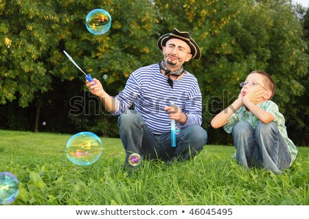 Man with drawed beard and whiskers is blowing soap bubbles. his son is looking on little soap bubble stock photo © Paha_L