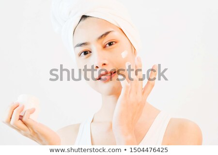 Beautiful female with towel on her head using face cream Stock photo © deandrobot