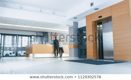 Woman receptionist in medical coat at reception desk in hospital Stock photo © vectorikart