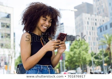smiling pretty young woman using smartphone outdoors stock photo © deandrobot