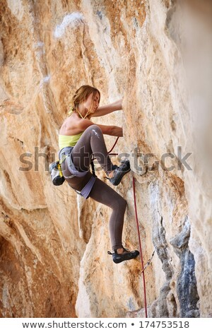 Female rock climber clinging to a cliff. stock photo © gregepperson